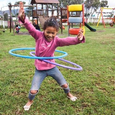 Niña jugando al hula-hula en centro de cuidado de nuestro voluntariado social en Sudáfrica.